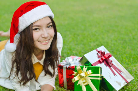 christmas ground: Portrait of young beautiful woman in santa claus hat with red christmas gift boxes Stock Photo