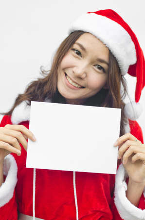 Girl in Santa holding banner. Cute funny photo closeup of christmas woman with copyspace. Isolated on white background. photo