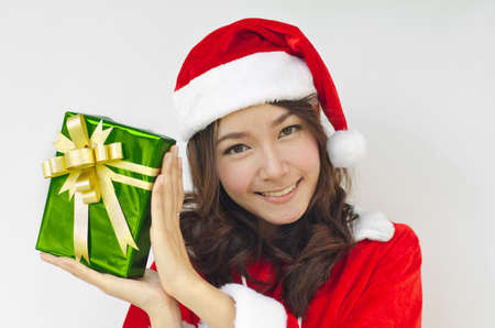 Portrait of young beautiful woman in santa claus hat with green christmas gift box with golden ribbons. photo