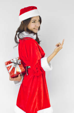 Portrait of young beautiful woman in santa claus hat with red christmas gift box with grey ribbons. Stock Photo - 16252616