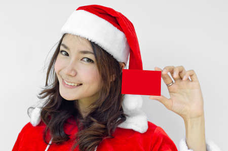 Girl in Santa holding red card. Cute funny photo closeup of christmas woman with copyspace. Isolated on white background. photo