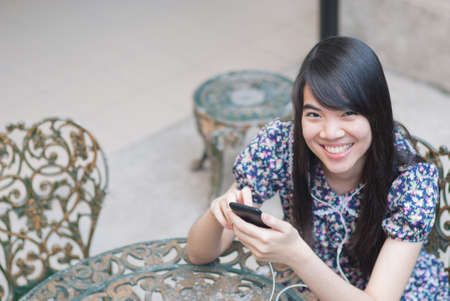 Young happy asian woman is calling with a mobile phone photo
