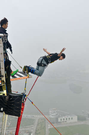 Macau Tower,Macau,China - MAY 8: a visitor jumped from Macau tower on May 8 2013. At 233 meters, the tower offers the second highest commercial bungee jump in the world.