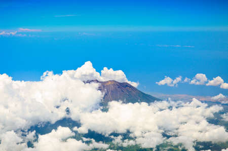 surrounds: Aerial view of volcano Gunung Agung in Bali. Low clouds surrounds it