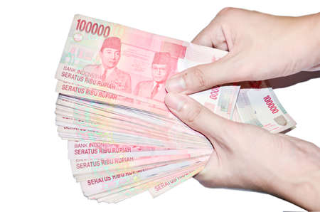 money wallet: woman hand holding money Indonesia, isolated on white background