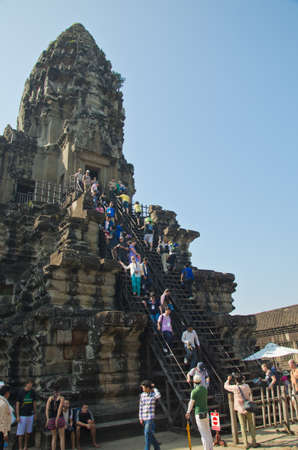 ANGKOR, CAMBODIA - JAN 4: Unidentified tourists climb to a praying tower at Angkor Wat. It is a part of the ancient Khmer complex Angkor, a UNESCO World Heritage Site, Jan 4, 2014, Angkor, Cambodia.