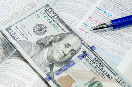 Dollar banknote and dictionary Stock Photo