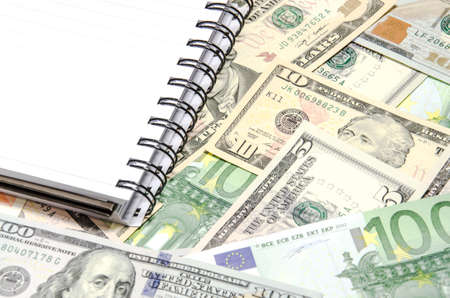 notepad on dollars and euros background photo