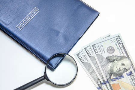 notebook with us dollars and magnifying glass photo