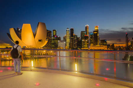 SINGAPORE, SINGAPORE - MAY 13: The skyline of Singapore lit up at night with the ArtScience Museum in the foreground. Photo taken May 13, 2014 in Singapore, Singapore.