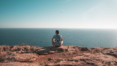 Boy looking at the sea on the horizon as he thinks about his life and summer.