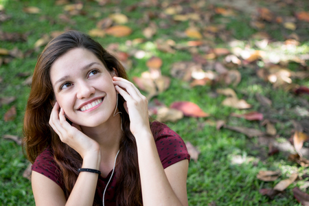 Beautiful woman outdoors listening to music with headphones and looking up pensive but happy