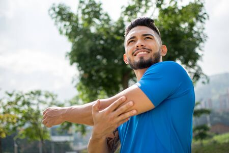 Handsome young man exercising outdoors stretching his arms and looking very happy