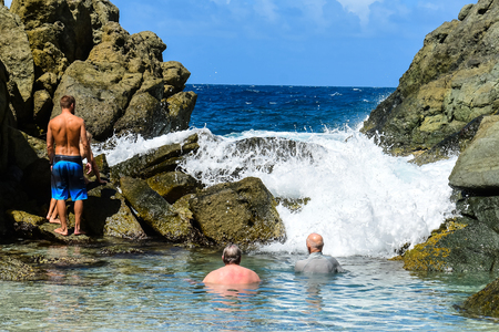 Bathers enjoying the surf rolling over the rocks in the Bubble Pool on Jost Van Dyke in the British Virgin Islands.