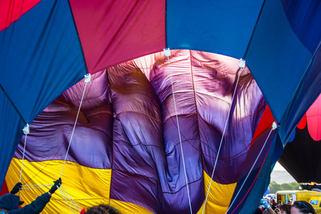 Ground crew holds guys whil the burner inflates this colorful hot air balloon Banco de Imagens
