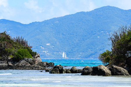 View from British Virgin Islands beach looking across channel at sailboat underway
