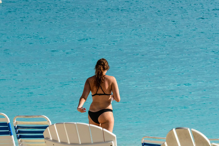 Wearing black bikini and walking away from the beach chairs in the foreground