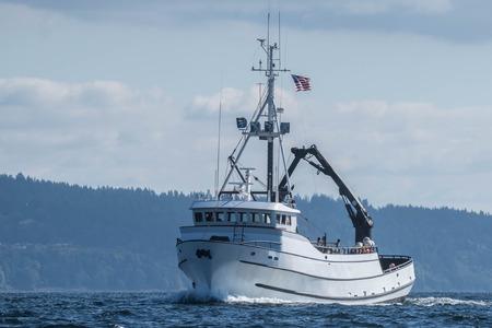 Krab vissersvaartuig Paragon onderweg onder licht bewolkte hemel en kalme zeeën in Puget Sound.