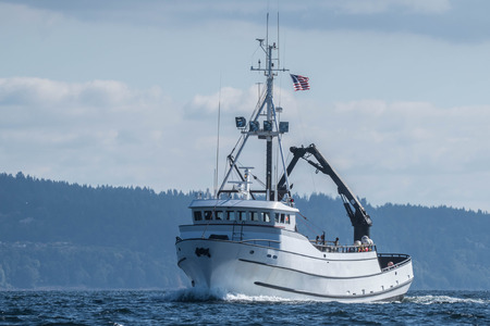 Crab fishing vessel Paragon underway under lightly cloudy skies and calm seas in Puget Sound.