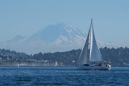 Sailing yacht out for afternoon sail on Puget Sound with Mount Rainier in the background.