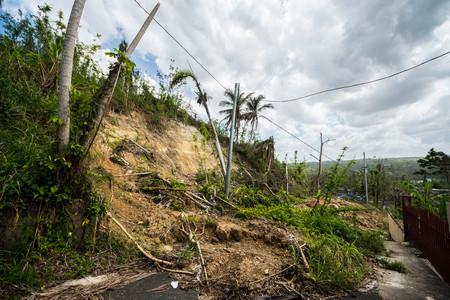 Roadway covered with mudslide from saturated hillside along highway in Puerto Rico Foto de archivo