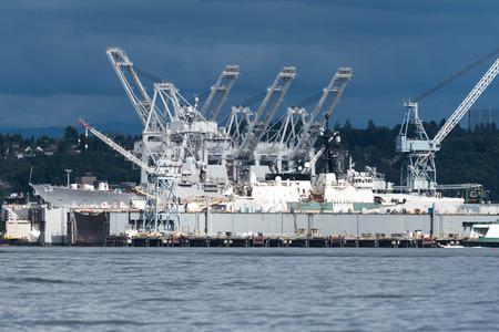 미국 해군 함정과 미국 해안 경비대 함선은 흐린 날에 시애틀에서 가장 큰 조선소에서 밝은 햇빛으로 작업 중입니다.