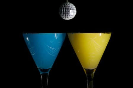 ingestion: Two drinks in the dark on a party night on black background