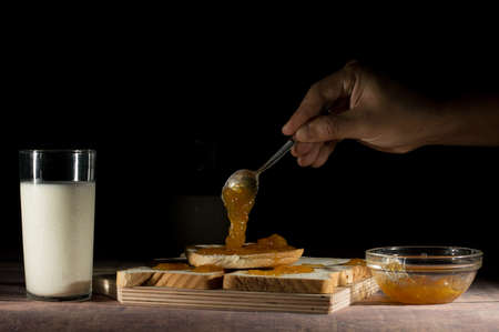 healthful: spreading jam on slices of bread with milk on the table on black background