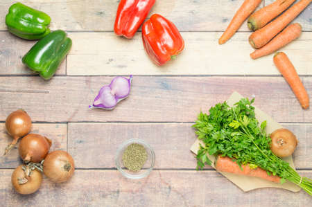 healthful: onions, peppers, carrots, garlic, parsley ready to cook on the wooden table