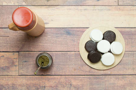 mate infusion: Top view of mate, alfajores on wooden table Stock Photo