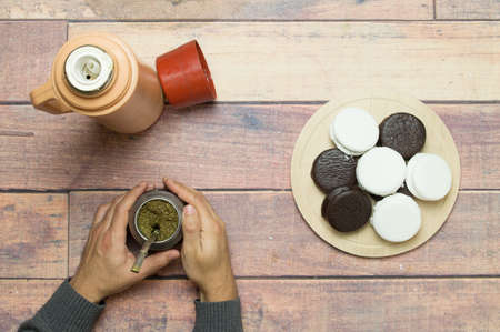Drinking mate with alfajores on the wooden table Stock Photo