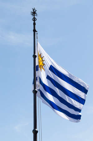 Flag of Uruguay waving in clear sky Stock Photo