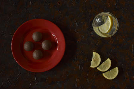 chocolates on the plate and drink with lemon slices served on the table