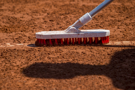 Worker cleans a line of tennis court with a brush Stock Photo
