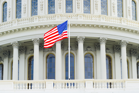 US Capitol Building dome detail with waving national flag - Washington DC, United States of America 写真素材