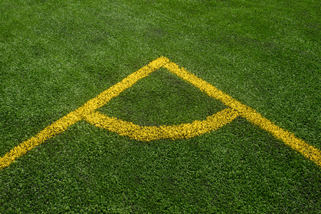 A top down angle view of yellow line on a green soccer field