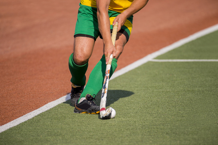 Field hockey player, in possesion of the ball, running over an astroturf pitch, looking for a team mate to pass to Stockfoto