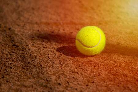 A lonely Tennis Ball on a Sand Court Stock Photo