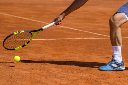 Male tennis player in action on the court on a sunny day Stock Photo