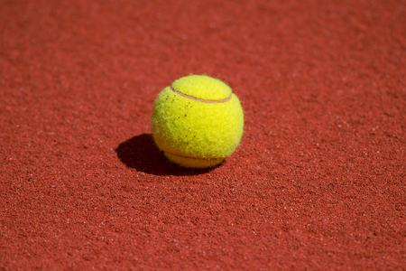 A lonely Tennis Ball on a red Sand Court