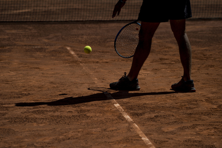 Male tennis player in action on the court on a sunny day 免版税图像