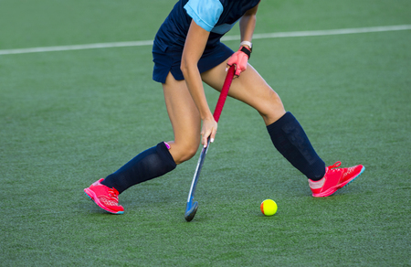 Young hockey player woman with ball in attack playing field hockey game Foto de archivo