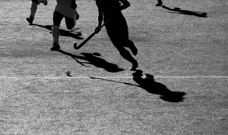 Silhouette. The shadow of a hockey players is running with a hockey stick on a hockey field.