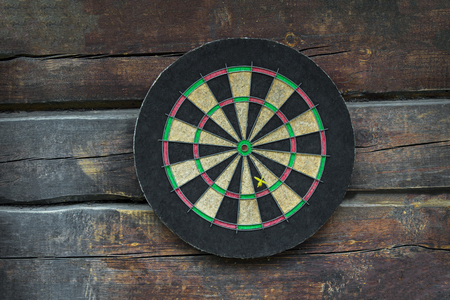 Dart board on old wooden table. Business concept.