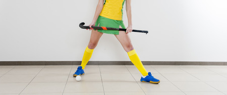 beautiful young woman holding hockey stick and ball against white background