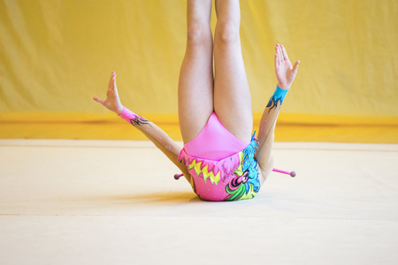 Girl with a rhythmic gymnastics clubs.Flexibility in acrobatics and fitness health Foto de archivo