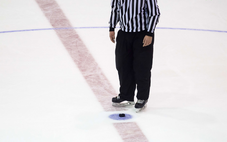 black hockey puck and referee legs on ice rink. Winter sport. Archivio Fotografico