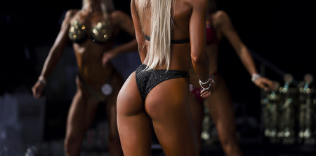 Fitness bikini girl on stage. Beautiful tanned female bodies.