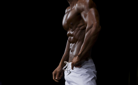 athlete bodybuilder in white summer shorts at competitions in beach bodybuilding