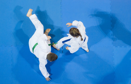 karate do kids fight against blue tatami background. Top View. Sport competition. 免版税图像